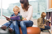 Teacher With Boy Reading Book In Library — Stockfoto