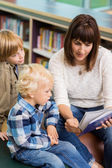 Teacher With Students Reading Book In Library — Foto de Stock