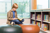 Boy Reading Book In Library — Stockfoto