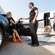 Stock Photo: Bodyguard Helping Elegant WomStepping Out Of Car