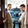 Pilots In Corporate Plane Cockpit — Stock Photo #38473399