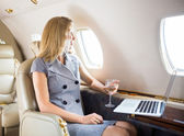 Businesswoman Looking Through Window Of Private Jet — Stock Photo