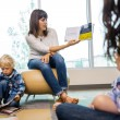 Teacher Reading Book To Students In Library — Stock Photo