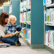 Boy With Teacher Reading Book In Library — Stock Photo #38558203