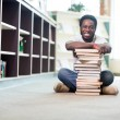 Happy Student Leaning On Stacked Books In Library — Stock Photo