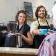 Stock Photo: Cafe Owners Serving Coffee To Woman At Counter