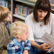 Teacher Reading Book For Students In Library — Stock Photo