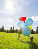 Boy With Helium Balloons Walking In Park — Stock Photo