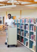 Bibliothécaire avec chariot de livres en librairie — Photo