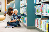 Boy With Teacher Reading Book In Library — Stock Photo