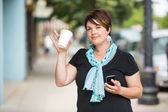 Woman With Mobilephone And Coffee Cup Waving — Stock Photo