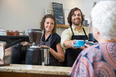 Cafe Owners Serving Coffee To Woman At Counter — Stock Photo