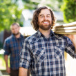 Stock Photo: Happy Carpenter With Coworker Carrying Planks Outdoors