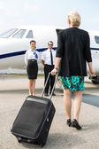 Businesswoman With Luggage Walking Towards Private Plane — Stock Photo