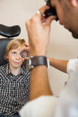 Boy Looking At Optician Examining His Eyes Through Lens — Stock Photo