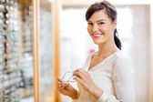 Woman Buying Glasses In Optician Store — Stock Photo