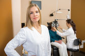 Eyecare Specialist With Colleague Examining Patient — Stock Photo