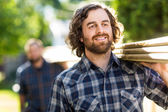Carpenter Smiling While Carrying Planks With The Help Of Coworke — Stok fotoğraf