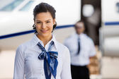 Pretty Stewardesses Smiling With Pilot And Private Jet In Backgr — Stock Photo