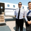 Stewardess And Pilot Standing Against Private Jet — 图库照片