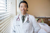 Confident Doctor With Patient At Hospital Room — Stock Photo