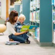 Boy And Teacher Reading Book By Bookshelf — Stock Photo