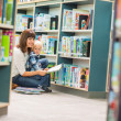 Teacher And Boy Reading Book By Bookshelf — Stock Photo #38762299
