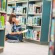 Stock Photo: Teacher And Boy Reading Book By Bookshelf