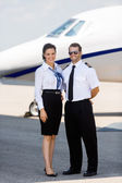 Airhostess And Pilot Standing Against Private Jet — Stock Photo