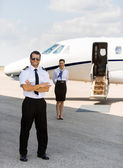 Full Length Pilot Against Stewardess And Private Jet At Terminal — Stock Photo