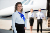 Airhostess Smiling While Pilot And Colleague Standing By Private — Stock Photo