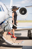 Wealthy Woman Disembarking Private Jet At Airport Terminal — Stock Photo