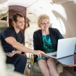 Business People Discussing Over Laptop On Private Jet — Stock Photo #38840965