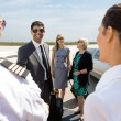 Stock Photo: Business People Greeting Pilot And Airhostess At Airport Termina