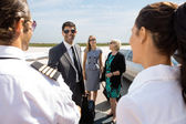 Business People Greeting Pilot And Airhostess At Airport Termina — Stock Photo