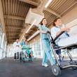 Stock Photo: Nurses Pushing Patients On Wheelchairs With Doctor At Corridor