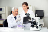 Scientist Reading Sample While Colleague Taking Notes — Stock Photo