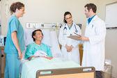 Medici discutendo note mentre paziente e infermiera a guardarli — Foto Stock