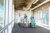 Medical Team With Patients On Wheelchairs At Hospital Corridor — Stock Photo