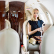 Wealthy Woman Holding Tablet Computer In Private Jet — Photo