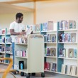 Librarian With Trolley Arranging Books In Library — ストック写真
