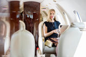Wealthy Woman Holding Tablet Computer In Private Jet — Stock Photo