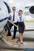 Confident Airhostess And Pilot Standing On Ladder Of Private Jet — Stock Photo
