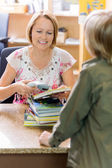 Librarian Scanning Books While Boy Standing In Library — Stock Photo