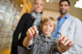 Boy Showing Glasses With Mother And Optician In Store — Stock Photo