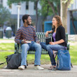 Students Sitting On Bench At University Campus — Stock Photo #39294571