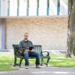 Stock Photo: Mid Adult Student Sitting On Bench At Campus