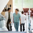 Stock Photo: Doctor And Nurse Discussing While Walking On Stairs