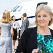 Stock Photo: Portrait Of Confident Businesswoman Against Private Jet
