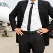 Stock Photo: Entrepreneur Standing In Front Of Private Jet And Car